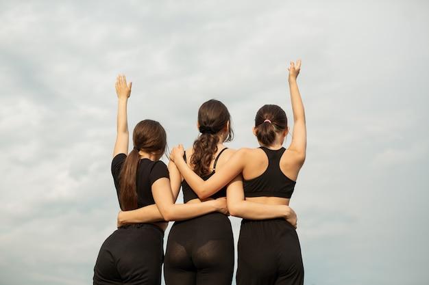 Três mulheres jovens atléticas com os braços levantados contra Foto Premium