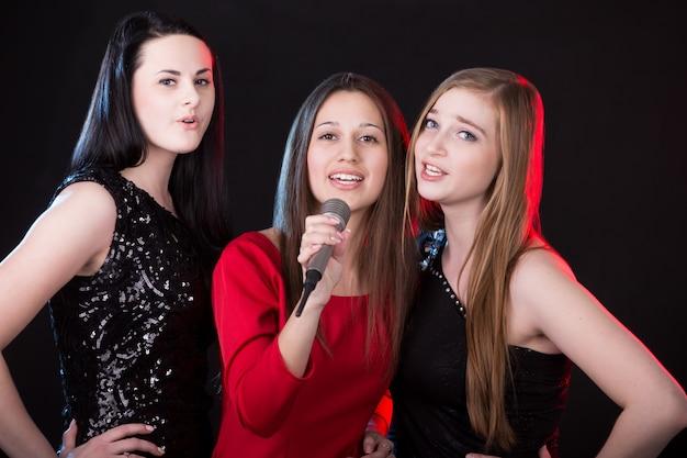 Três mulheres jovens atraentes cantando