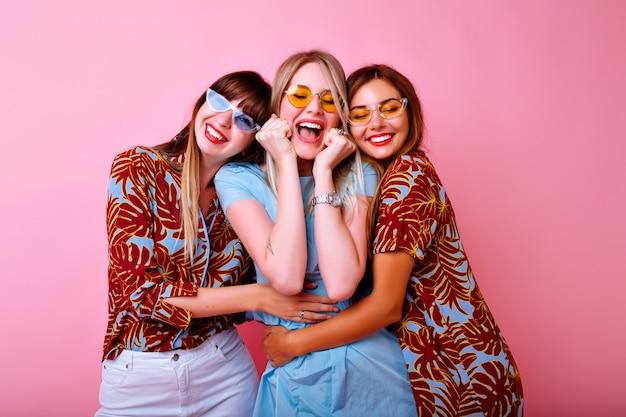 Três mulheres jovens bonitas felizes fazendo selfie, grupo de melhores amigos se divertindo, roupas de correspondência de cores com impressão tropical na moda elegante e óculos vintage, parede rosa.
