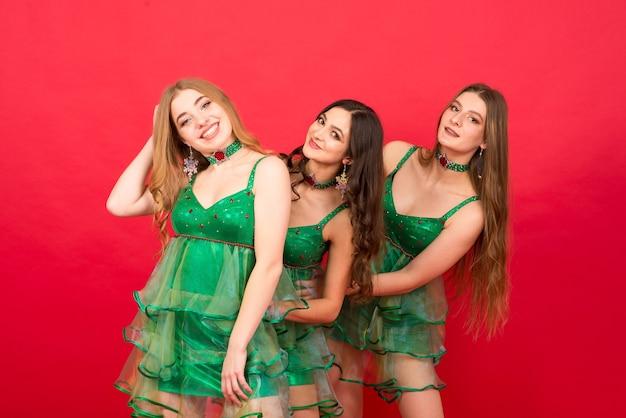 Três mulheres jovens com fantasia de árvore de natal sexy em fundo vermelho em estúdio