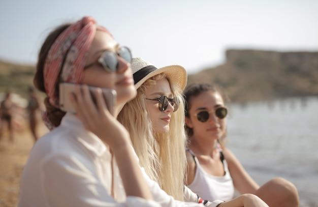 Três mulheres jovens de óculos na praia, uma falando ao telefone