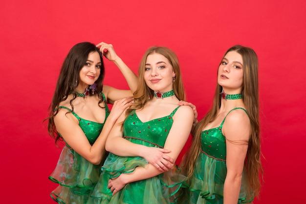 Três mulheres jovens em uma fantasia sexy de árvore de natal em fundo vermelho, estúdio