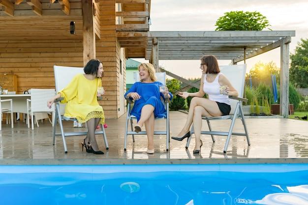 Três mulheres maduras de meia-idade estão se divertindo e conversando
