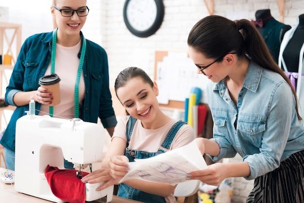 Três mulheres na fábrica costuram roupas novas.