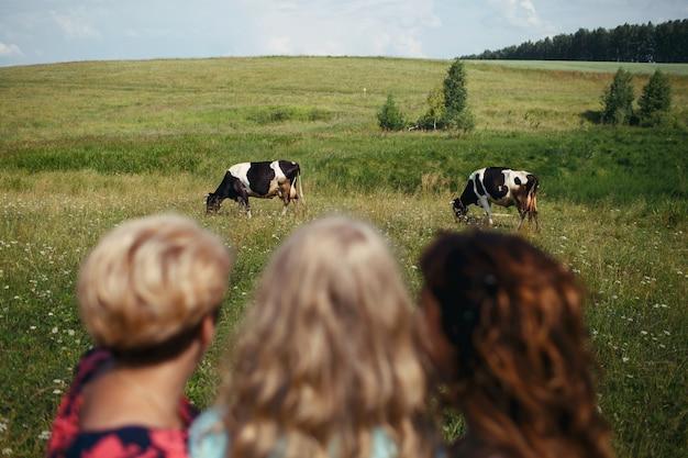 Três mulheres olham vacas pastando em um campo verde