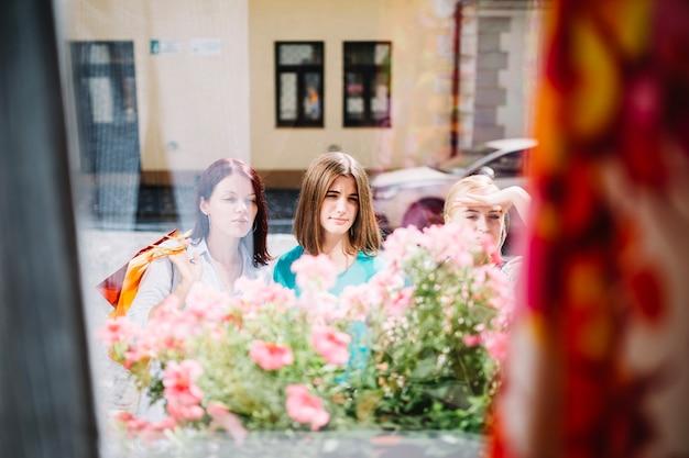 Três mulheres olhando através da vitrine