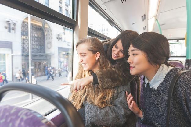 Três mulheres olhando pela janela. o ônibus