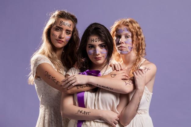 Três mulheres pintadas com palavras e se abraçando