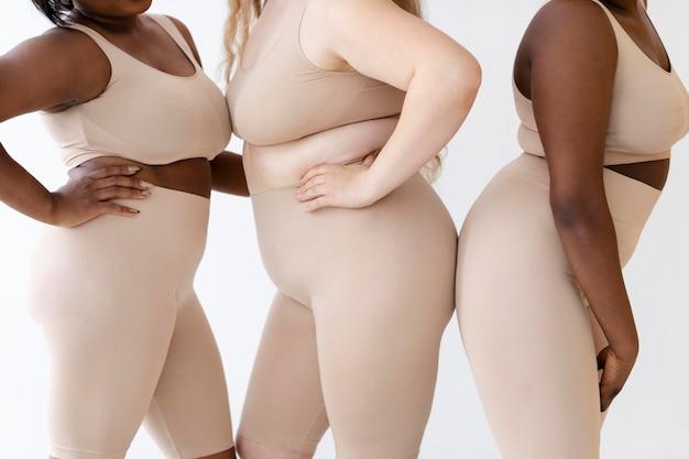 Três mulheres posando juntas usando um modelador de corpo