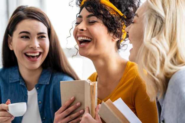 Três mulheres rindo junto com um livro e uma xícara de café