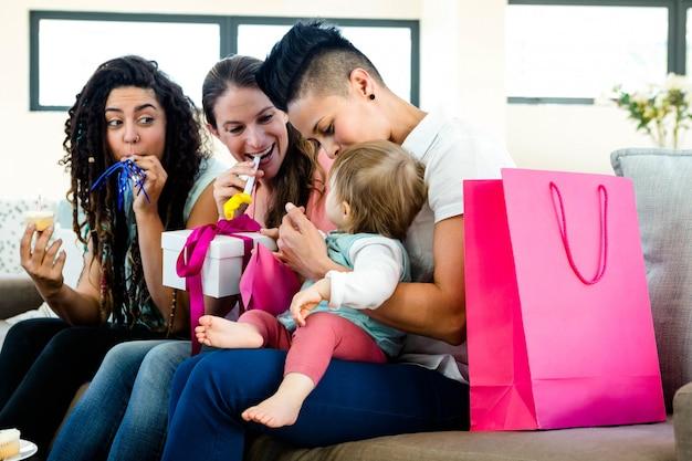 Três mulheres sentadas em um sofá comemorando um primeiro aniversário de bebês