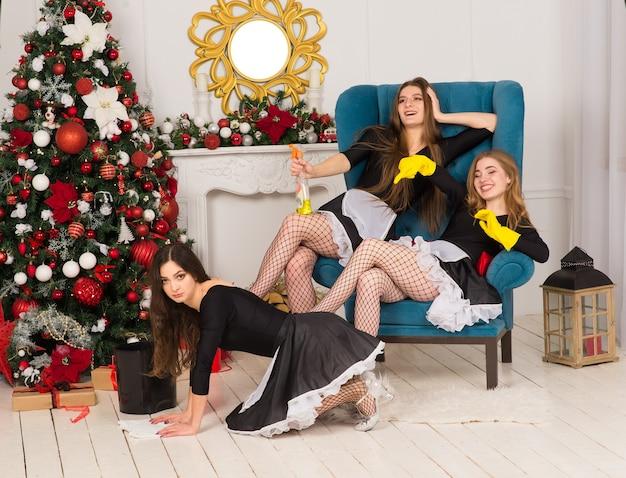 Três mulheres sexy em fantasia de empregada doméstica em um interior de natal, árvore do abeto, ano novo.
