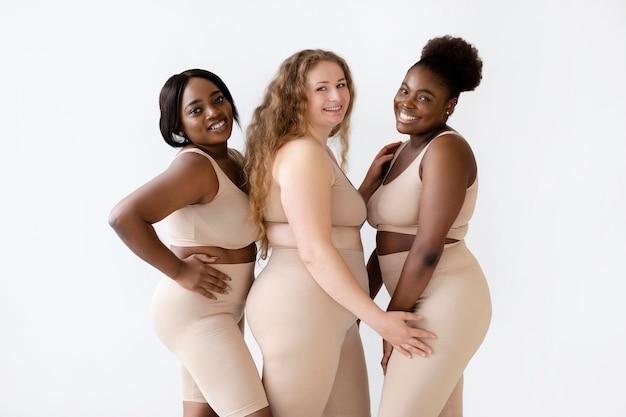 Três mulheres sorridentes posando juntas em modeladores de corpo