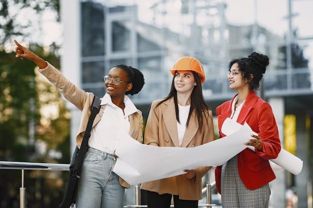 Três mulheres trabalhando como arquitetas em uma construção e tomando uma decisão sobre a planta de um edifício
