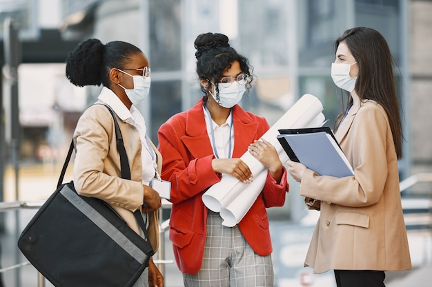 Três mulheres trabalhando como arquitetas em uma construção. pessoas que tomam uma decisão sobre a planta de um edifício. conceito de quarentena
