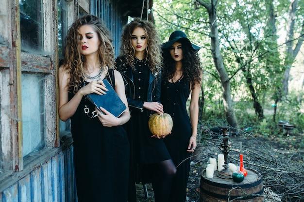 Três mulheres vintage como bruxas em poses perto de um prédio abandonado na véspera do halloween