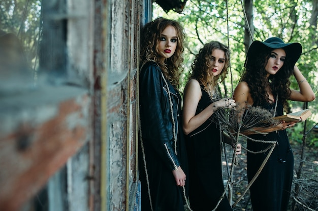 Três mulheres vintage como bruxas posam em frente a um prédio abandonado com livros nas mãos na véspera do halloween