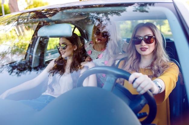 Três namoradas jovens viajando em um carro