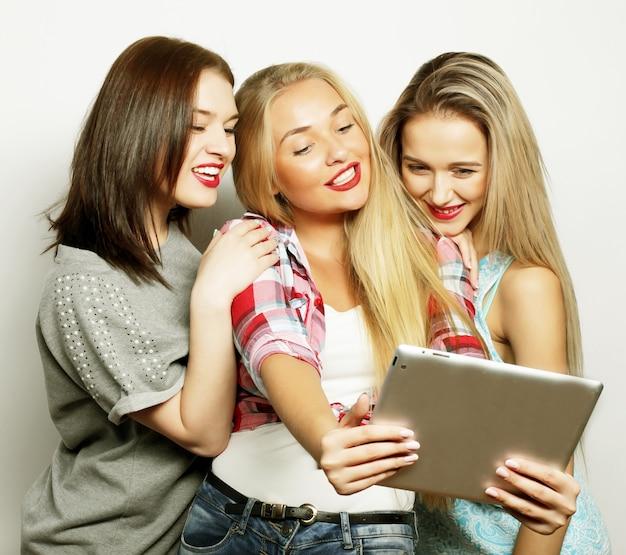 Três namoradas tirando selfie com tablet digital