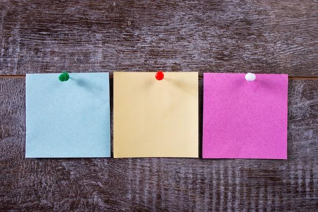 Três notas coloridas fixadas com tachinhas na parede de madeira