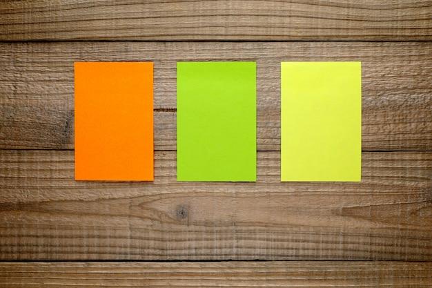 Três notas post-it coloridas na madeira