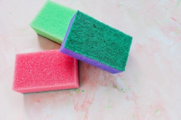 Três novas esponjas coloridas para lavar pratos em fundo rosa. doméstico e limpeza