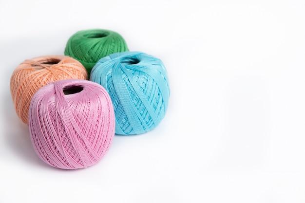 Três novelos de fios de lã sobre um fundo branco, rosa, verde, pêssego e azul isolado no branco