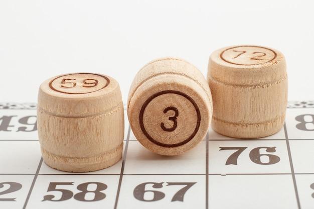 Três números de barril de madeira e cartas para um jogo de loteria em um fundo branco. vista de perto
