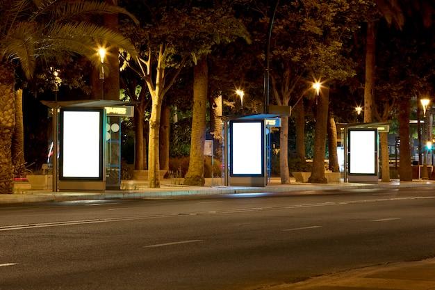 Três outdoor com luz no centro da cidade à noite
