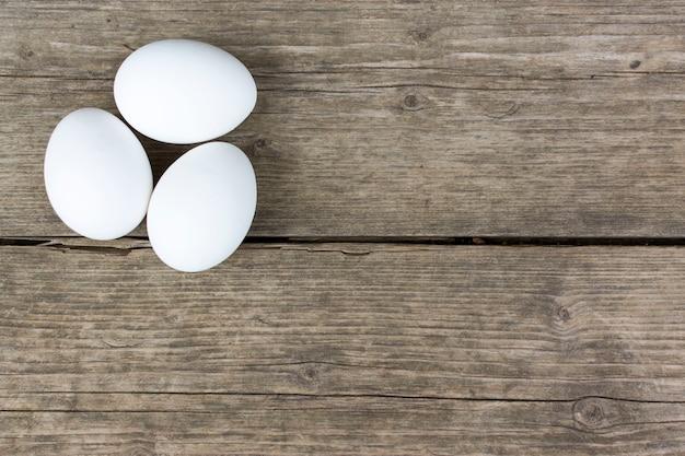 Três ovos de galinha brancos crus na velha mesa de madeira vintage