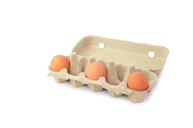Três ovos de galinha em uma caixa de ovos com distância, coronavírus, covid-19, distanciamento social. conceito de distanciamento social. com traçado de recorte