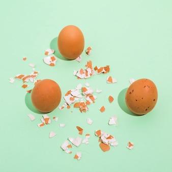 Três ovos de galinha marrom com casca quebrada na mesa