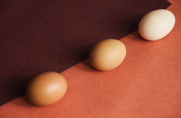 Três ovos de galinha são colocados em papel de cores naturais. a textura do papel e do ovo é bege. ovos de páscoa.