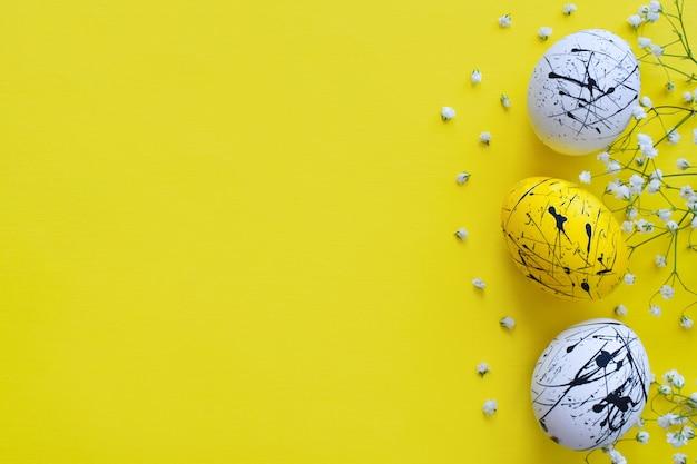Três ovos de páscoa e flores em um fundo amarelo. feliz páscoa. minimalismo. plano de fundo com uma cópia do espaço.