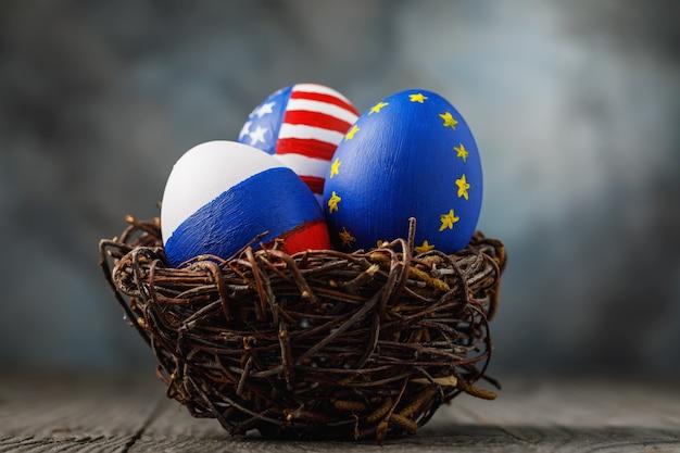 Três ovos de páscoa em um ninho pintado com as cores das bandeiras da rússia, américa e união europeia, em uma mesa de madeira.