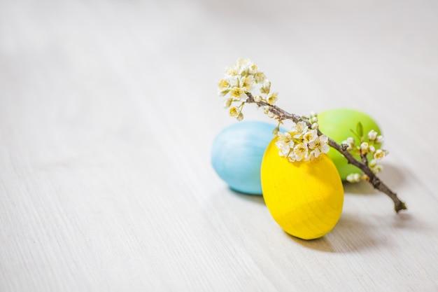Três ovos de páscoa perto de ameixa