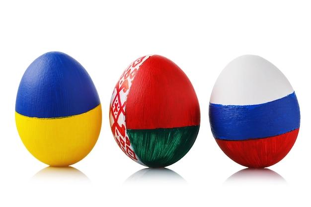 Três ovos de páscoa pintados com as cores das bandeiras da ucrânia, bielorrússia e rússia, isoladas em uma superfície branca