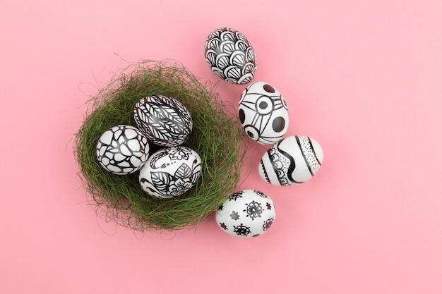 Três ovos de páscoa são pintados em preto e branco, abstração, mentem em um ninho verde. perto do ninho, há mais quatro ovos pintados. ovos de páscoa mentem sobre um fundo rosa. postura plana. copie o espaço