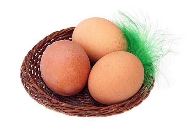 Três ovos em uma cesta e uma pena isolada