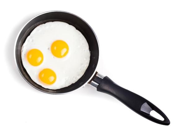 Três ovos fritos na panela de teflon sem óleo isolado no branco