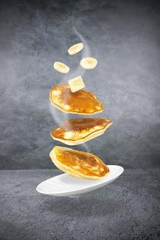 Três panquecas levitando com um pedaço de manteiga e rodelas de banana e um prato branco na superfície cinza