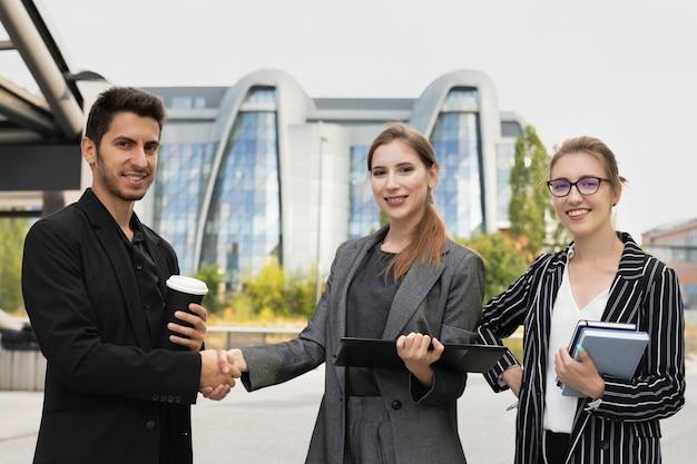 Três parceiros de negócios estão contra um prédio de escritórios. apertam as mãos, como sinal de negociações bem-sucedidas.