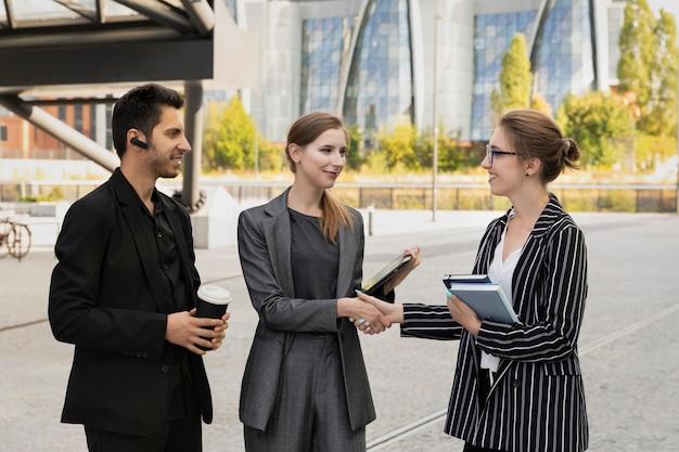 Três parceiros de negócios estão no contexto de um prédio de escritórios. apertam as mãos, como sinal de negociações bem-sucedidas.