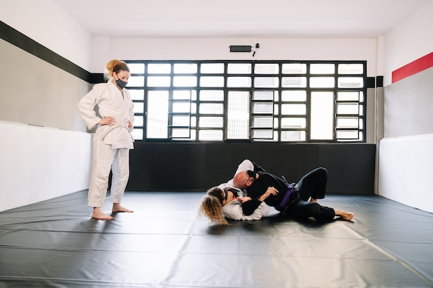 Três parceiros em um treinamento de artes marciais praticando técnicas no tapete de ginástica, todos usando máscaras faciais devido ao cobi 19