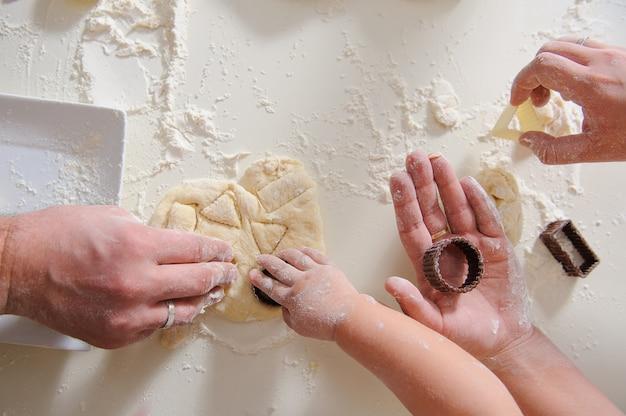 Três pares de mãos criam biscoitos caseiros, apenas as mãos. cortadores de biscoito para assar biscoitos com massa e farinha