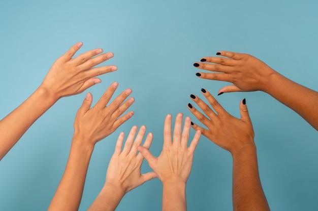 Três pares de mãos de mulheres jovens de várias etnias com cores de pele diferentes em azul