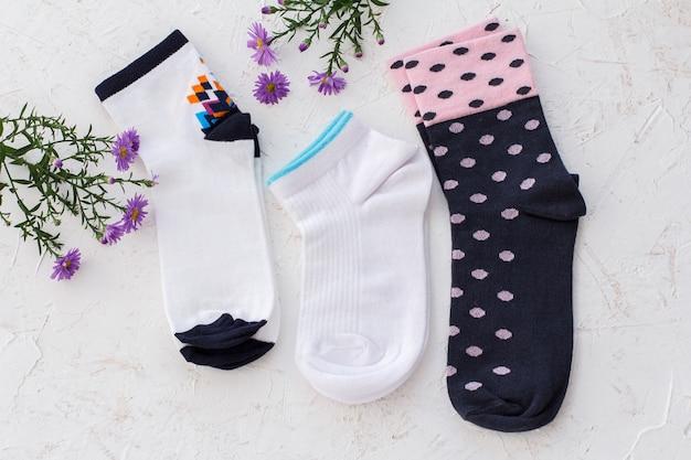 Três pares de meias femininas e flores sobre fundo branco estruturado, vista superior.