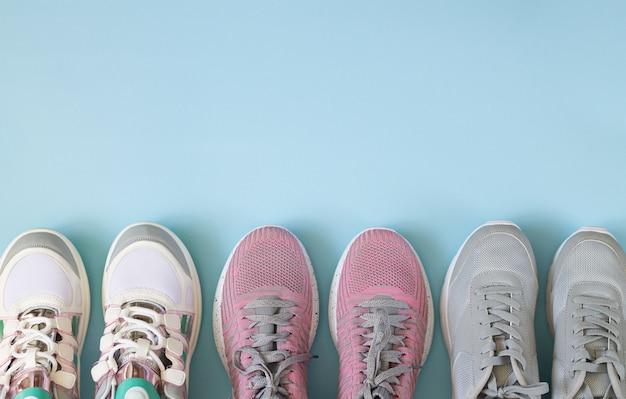 Três pares de sapatos de desporto vista superior sobre fundo azul claro, com espaço de cópia