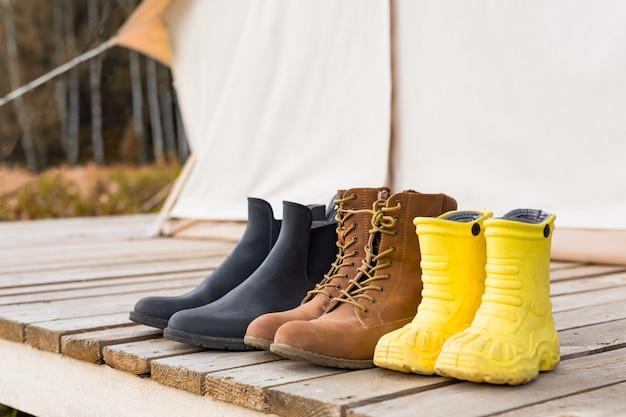 Três pares de sapatos perto de uma tenda de lona