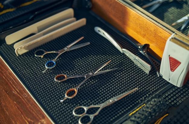 Três pares de tesouras e alguns pentes de cabelo no local de trabalho de um barbeiro
